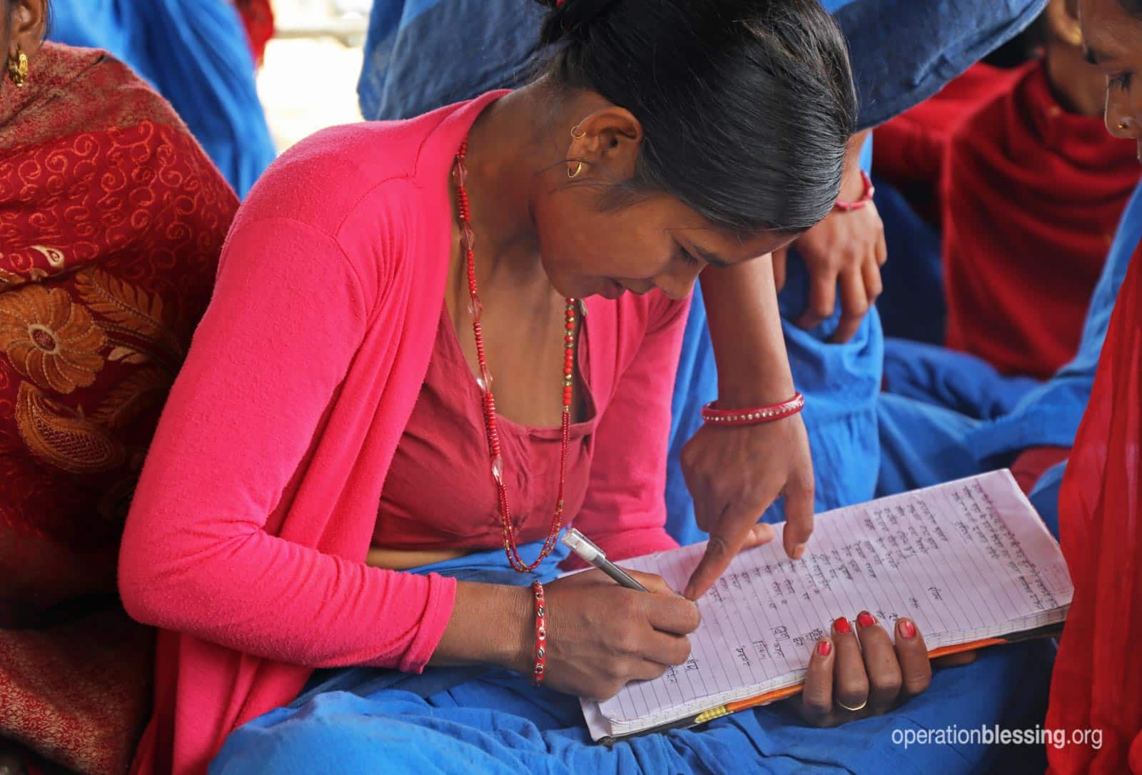 A woman fills out a form at the Mother Group.