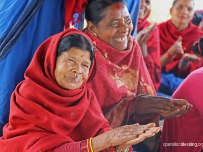 Two women clap in Nepal, thankful for Mother Group's programs that are empowering women.