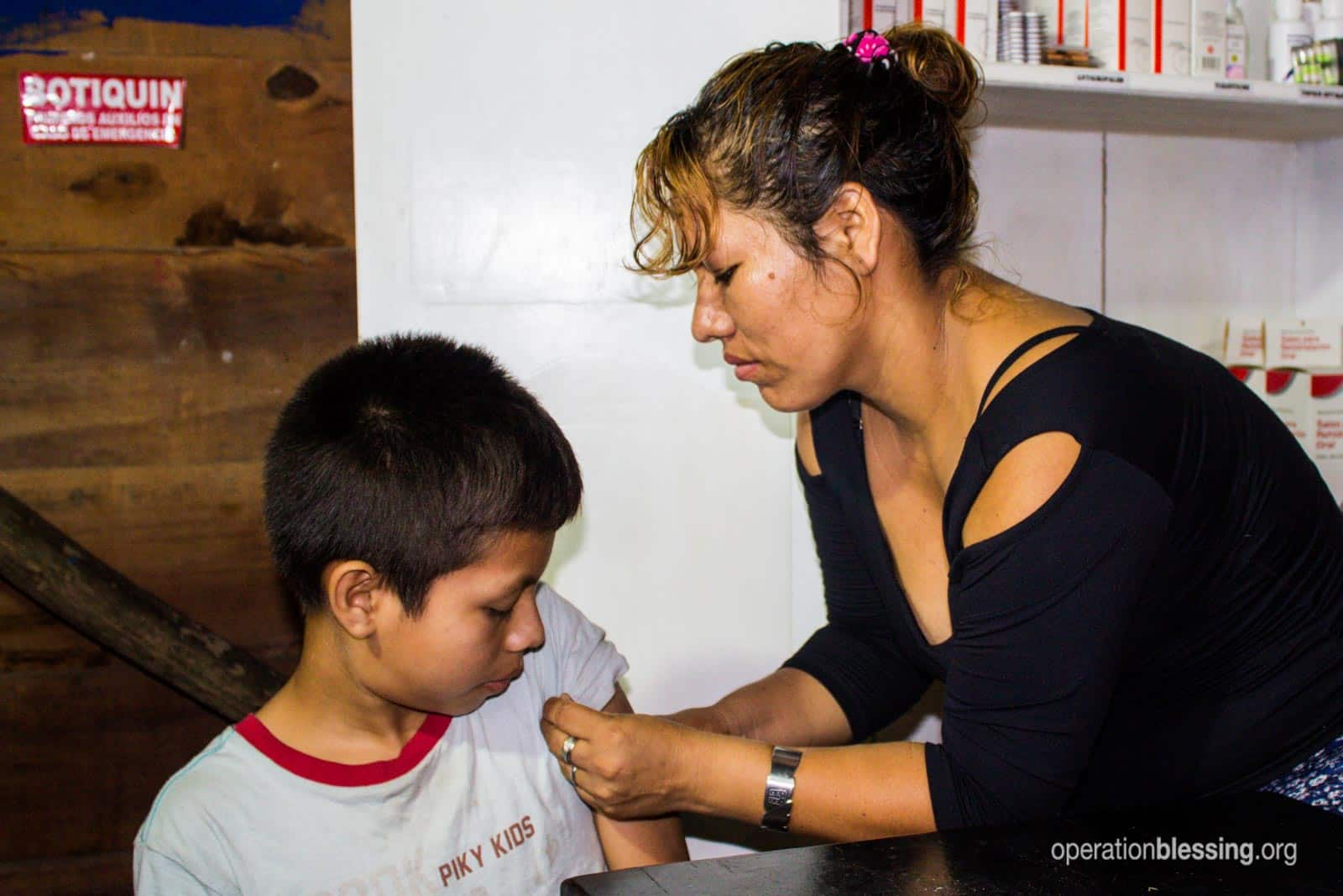 Lizeth tends to a little boy's arm.