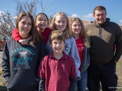This Tennessee family stands together smiling, thankful for the relief they've received.