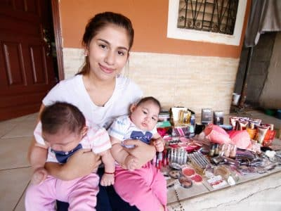 Sara holds her babies born with microcephaly in front of her new microenterprise.