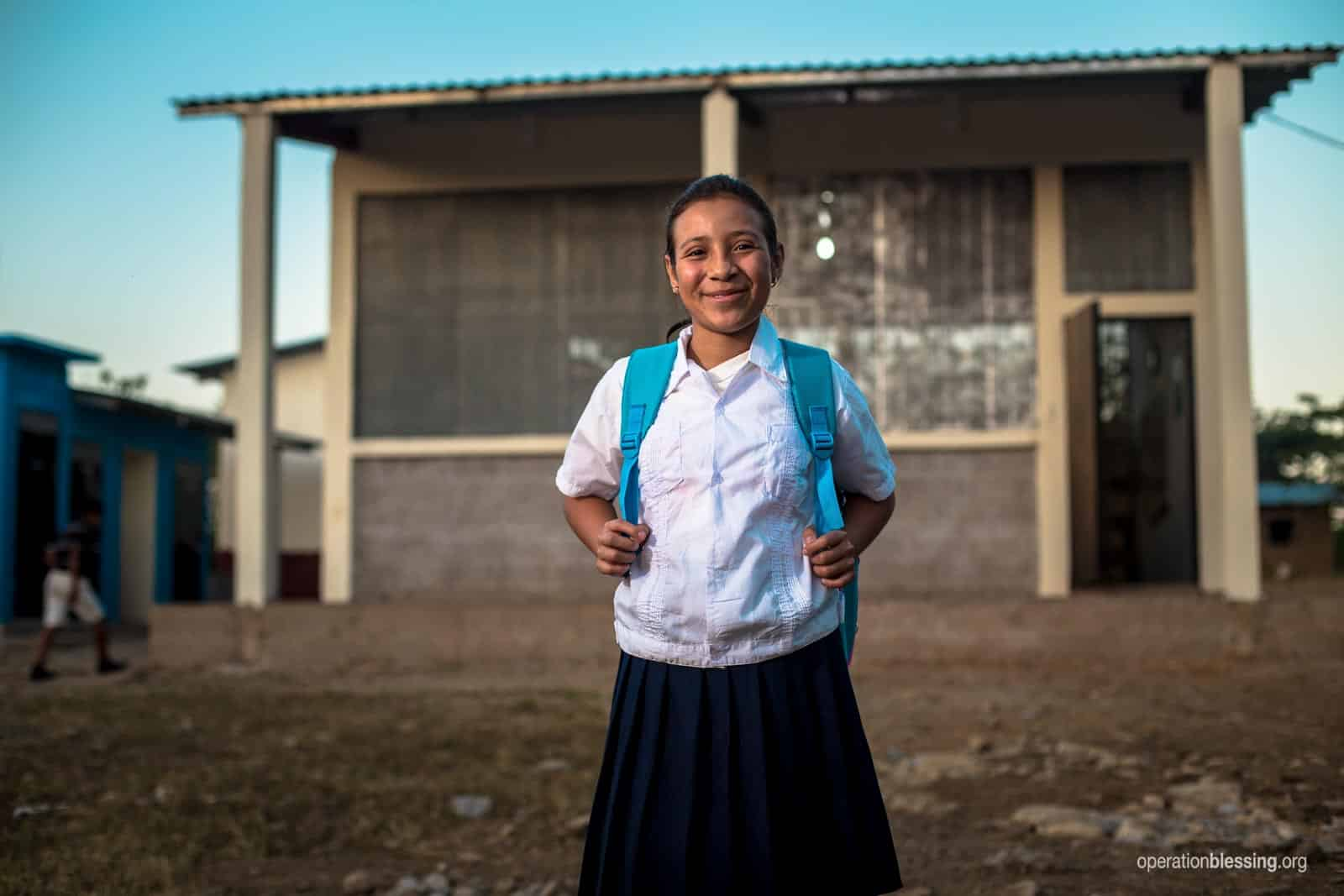 July happenings kicks off as twelve-year-old Stephany stands in front of the brand new school that Operation Blessing recently built in her community.