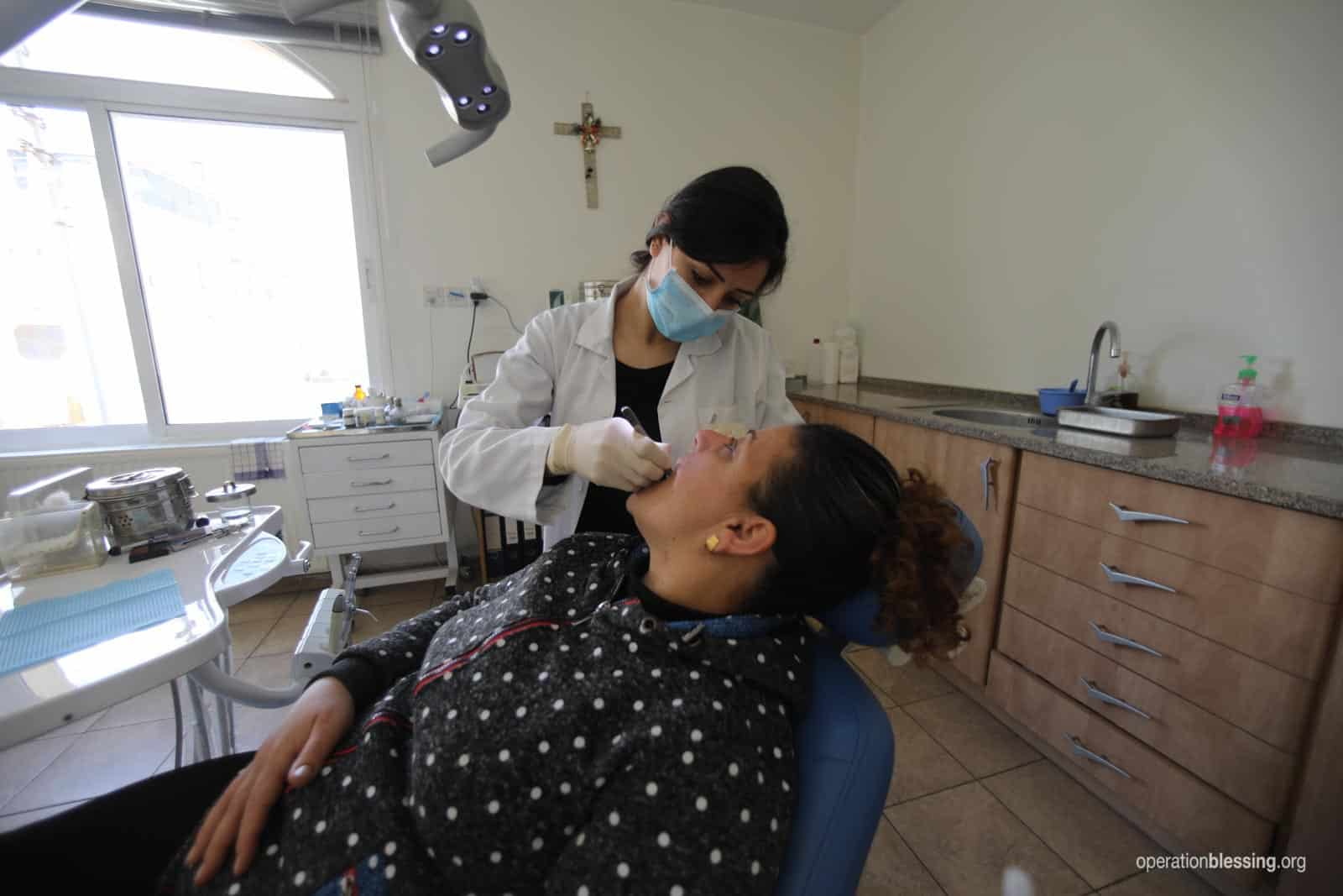 A woman receives a dental checkup at a medical clinic for Christian refugees supported by Operation Blessing.