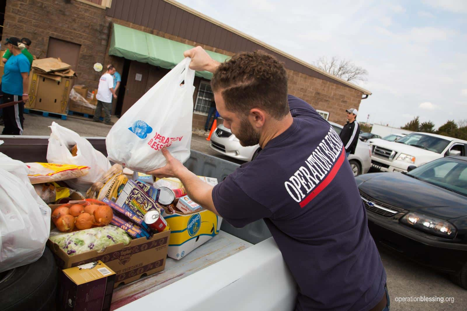 An Operation Blessing staff member helps load groceries into a truck at Joseph's Storehouse, an OBI-supported food pantry reaching vulnerable families in Tennessee.