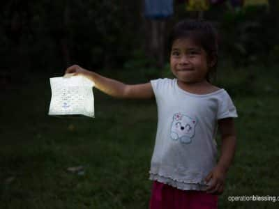 A girl holds one of the solar lights donated to her family.