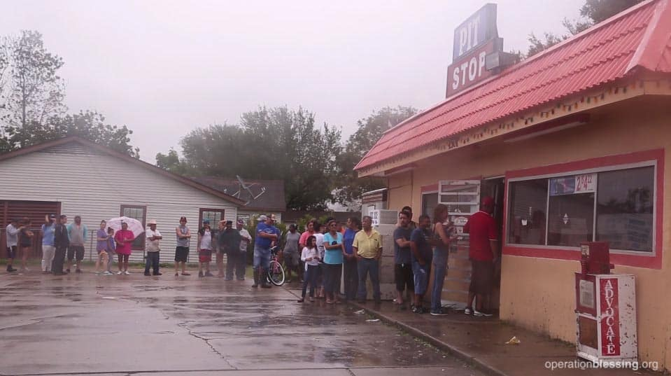 People in Texas stand in a long line wrapping around the parking lot to get into one of the only open convenience stores for supplies.