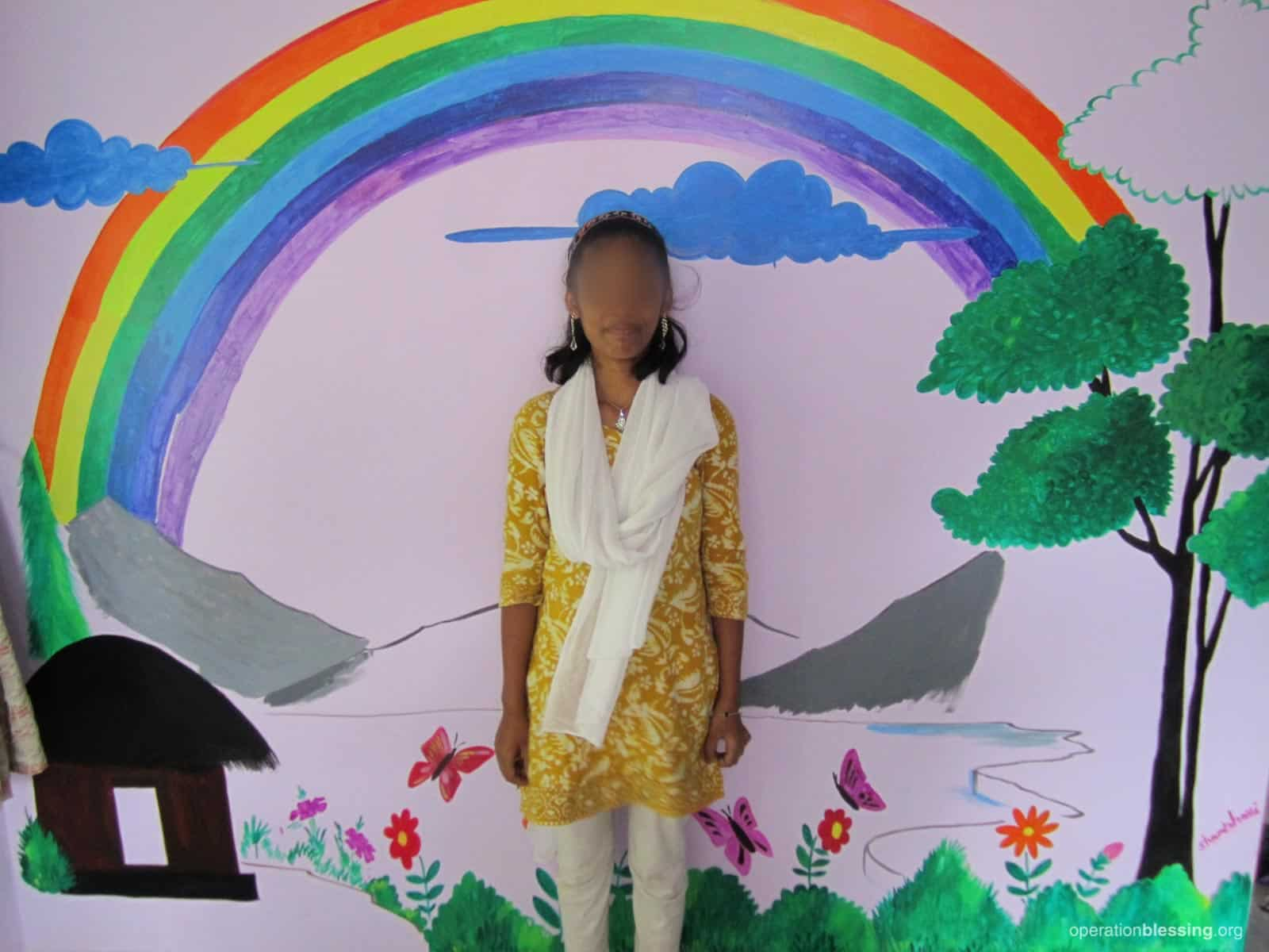 Naseen stands under a painted rainbow, no longer a prisoner of the darkness of the brothel.
