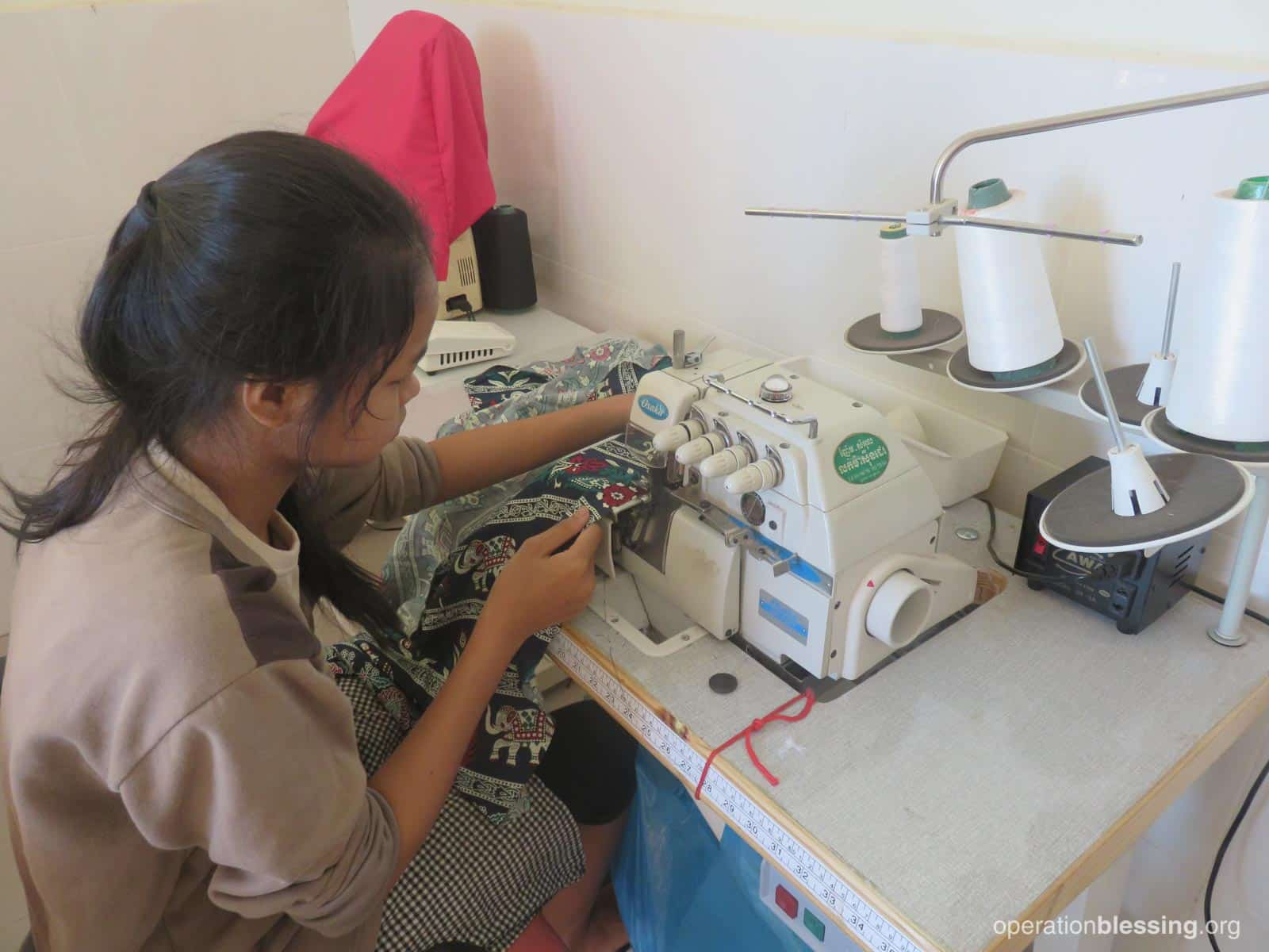 One of the girls works at a sewing machine as Operation Blessing and The Apple of God's Eyes help her weave a new tapestry of hope for her life.