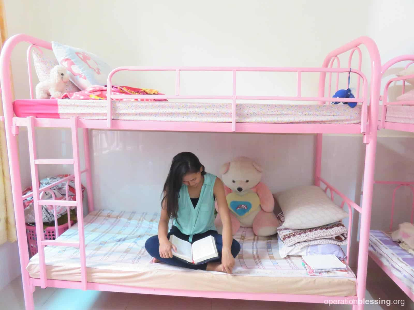 A young woman reads on her bed, part of the tapestry of hope provided to at-risk girls.