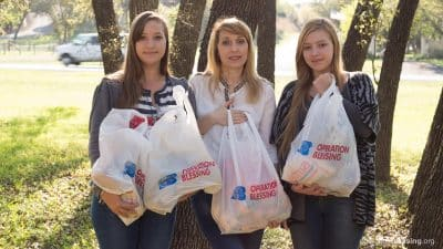 Tatiana and her daughters hold bags of food, part of the compassionate relief they have received from Hill Country Daily Bread.