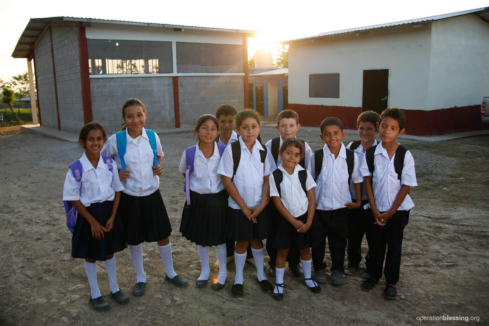 Honduran children stand with their new uniforms and backpacks in front of their new school.