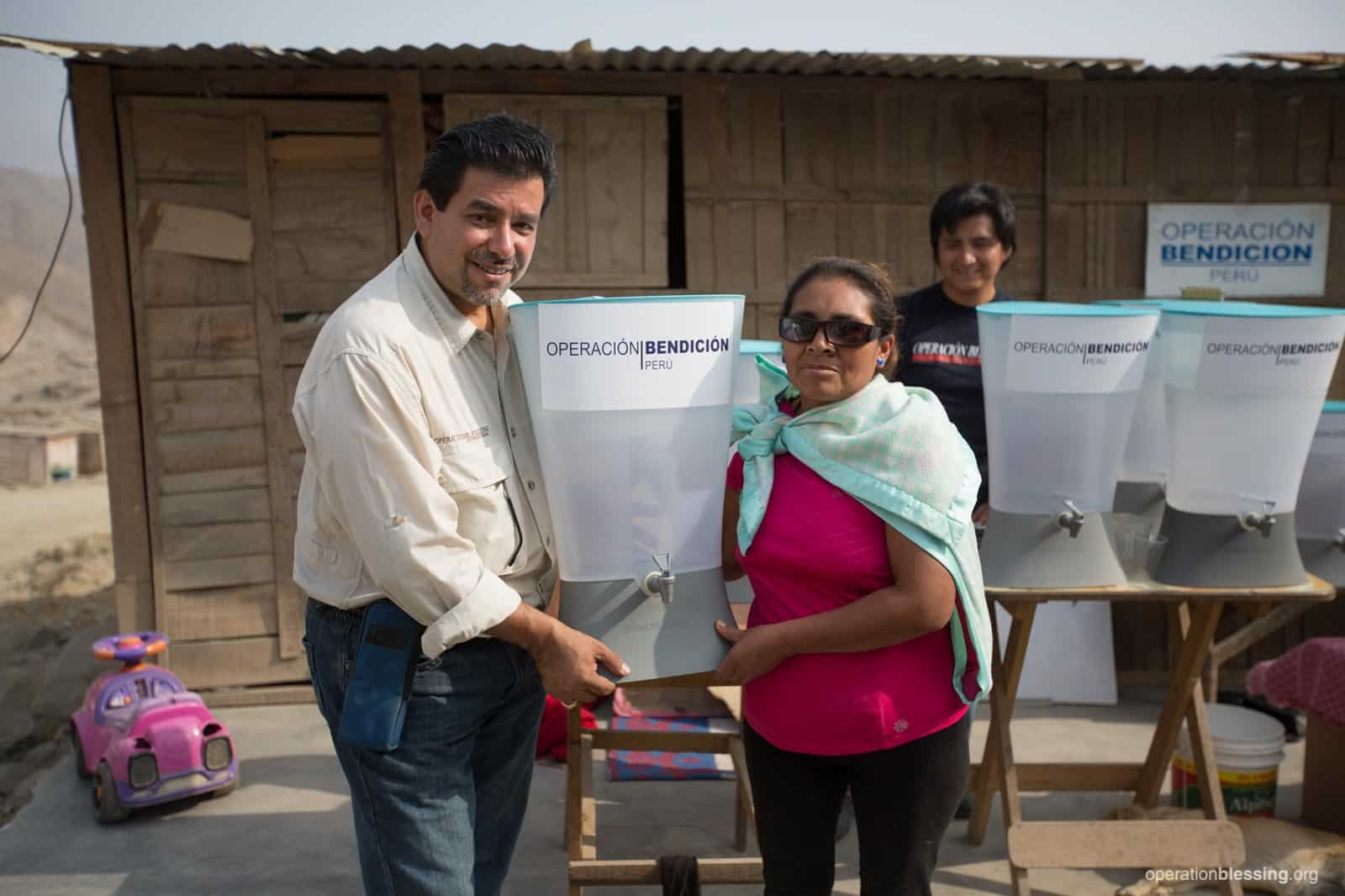 Operation Blessing's water programs manager, Ignacio Romero, distributes Kohler Clarity water filters to families in Terrazas del Vallecito, Peru.