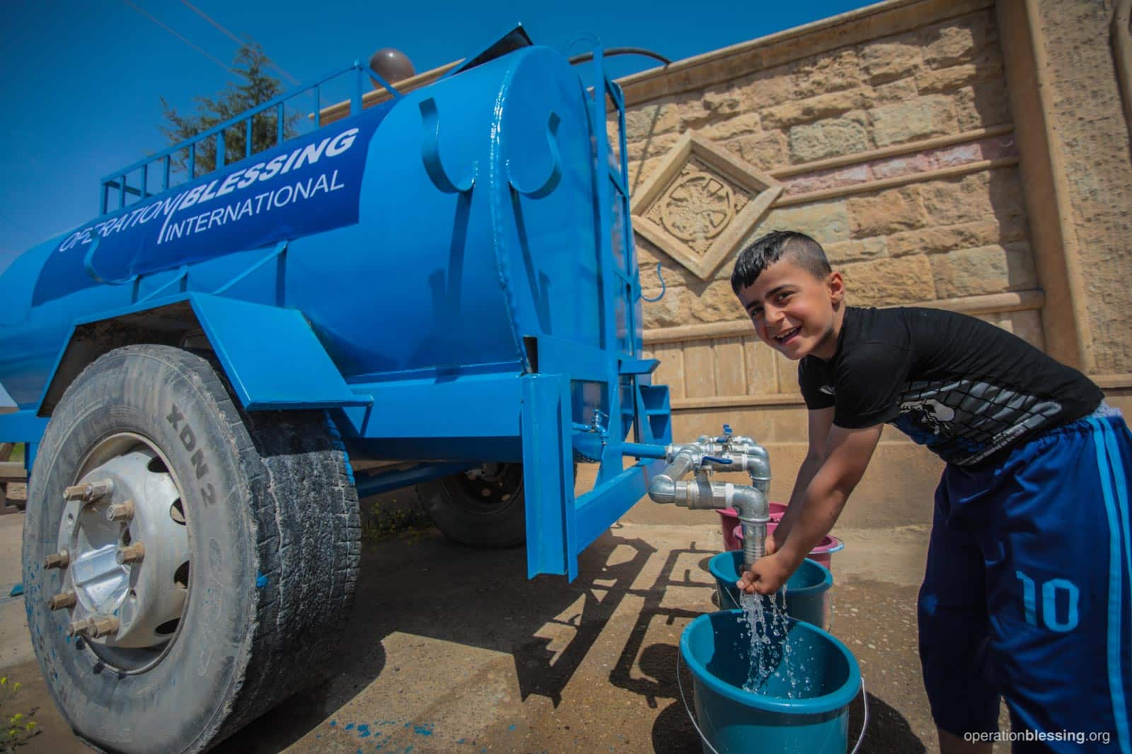 A boy washes his hands in water flowing from Operation Blessing's mobile water tank in Qaraqosh, Iraq.