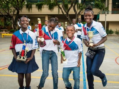 In August Happenings, students from Operation Blessing's chess program celebrate their victories at the national competition, holding two first place and two second place trophies!
