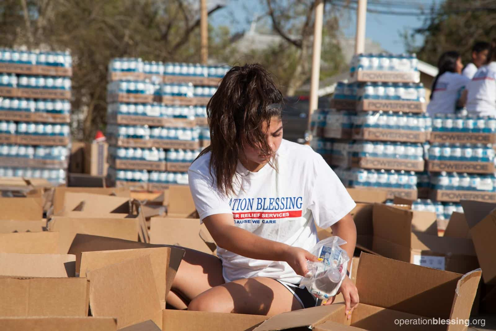 A young woman sits amid boxes of supplies with drinks stacked behind her, helping victims of Hurricane Harvey.