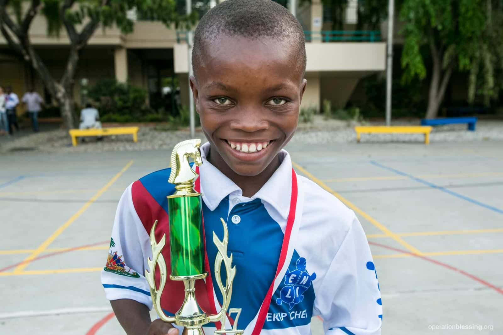 Haitian student receives chess trophy because Operation Blessing is investing in Haiti's children.