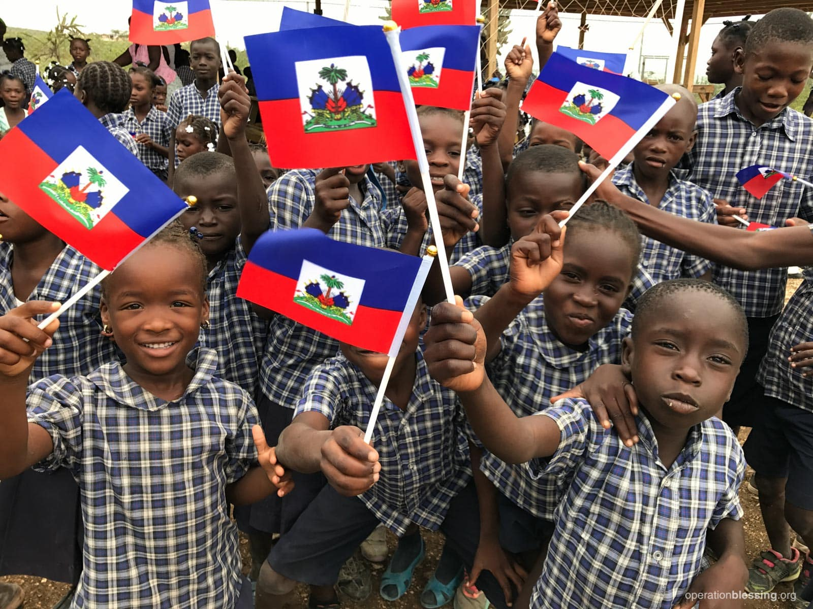 Operation Blessing students in Haiti wave their national flags.