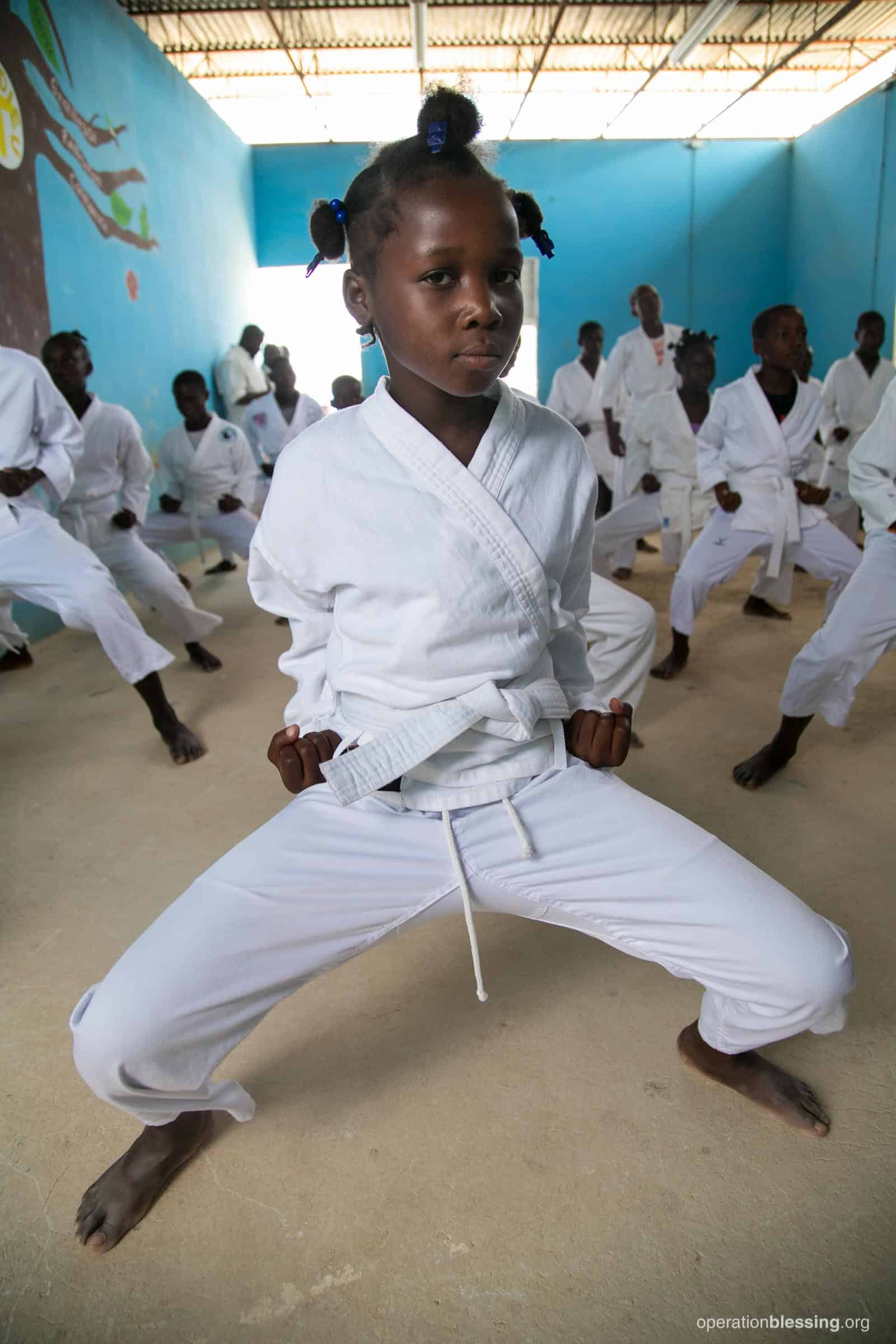 A young girl practices martial arts because Operation Blessing is investing in Haiti's children.