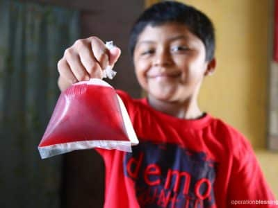 Selvin holds bags of traditional Guatemalan ice cream called topogigios to sell.