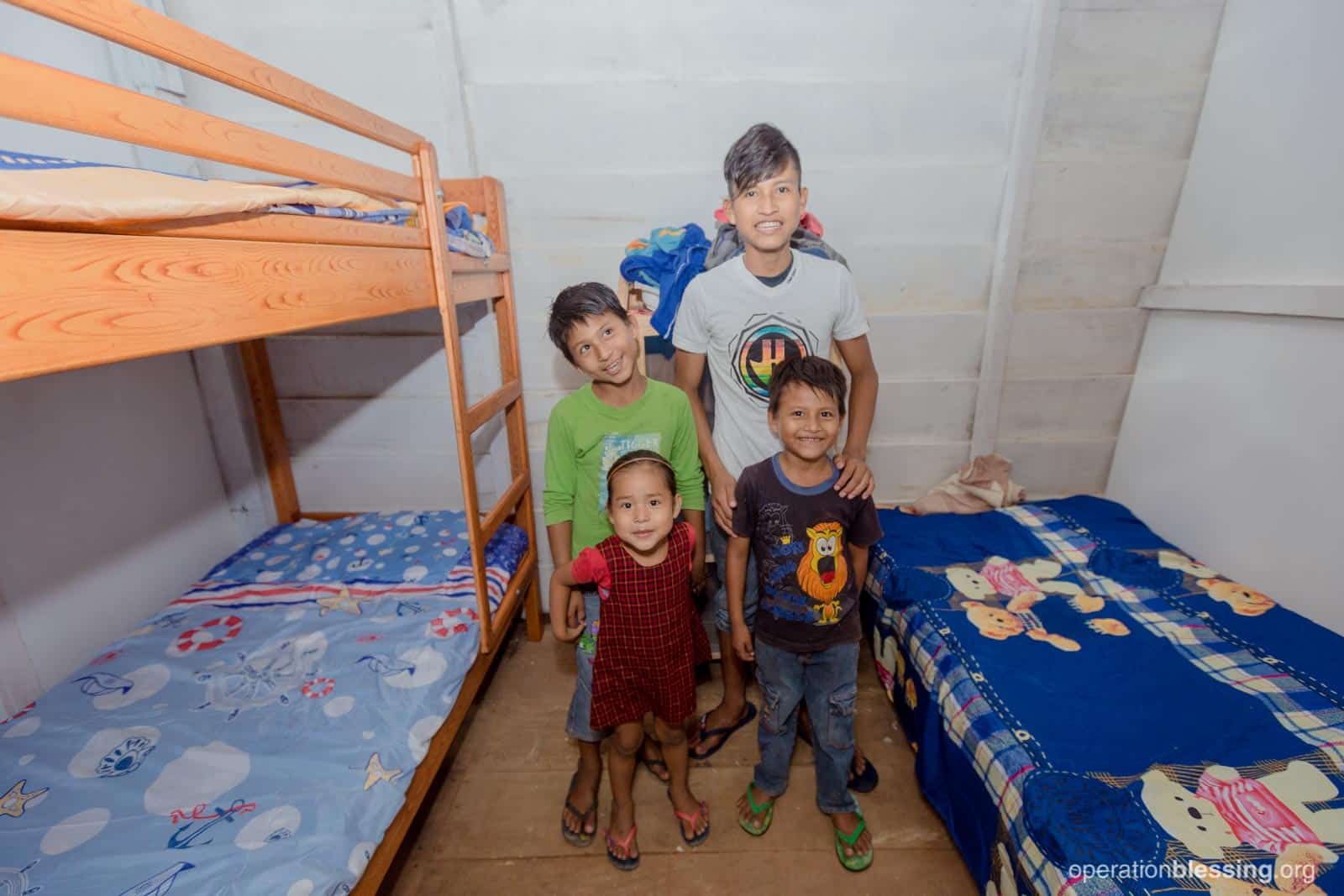 Margot's four children, standing in their new bedroom, can feel safe in their new home.