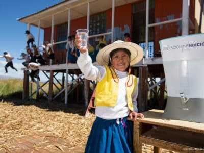 Zaida, from the Floating Uros Islands in Peru, holds a glass of safe water thanks to Operation Blessing.