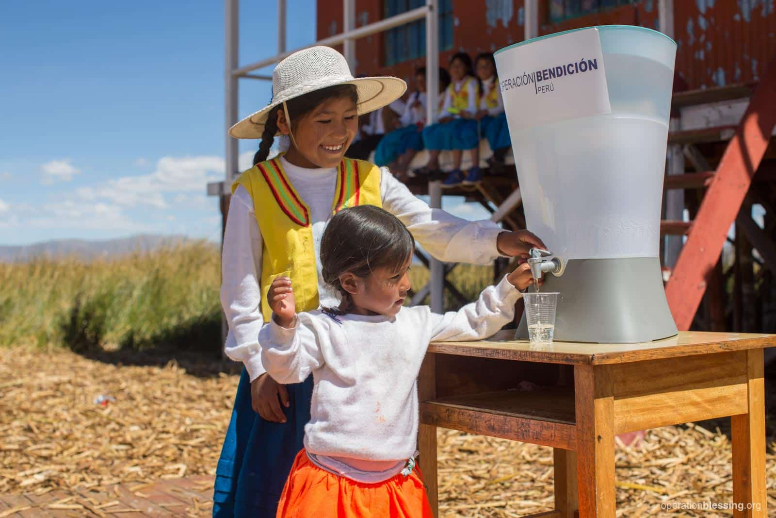 Zaida helps a younger child get safe water from their new Kohler Clarity filter.