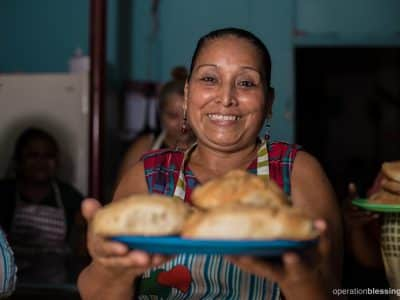 Balvina holds a fresh loaf of bread she made through a baking program that is giving her family a brighter future.