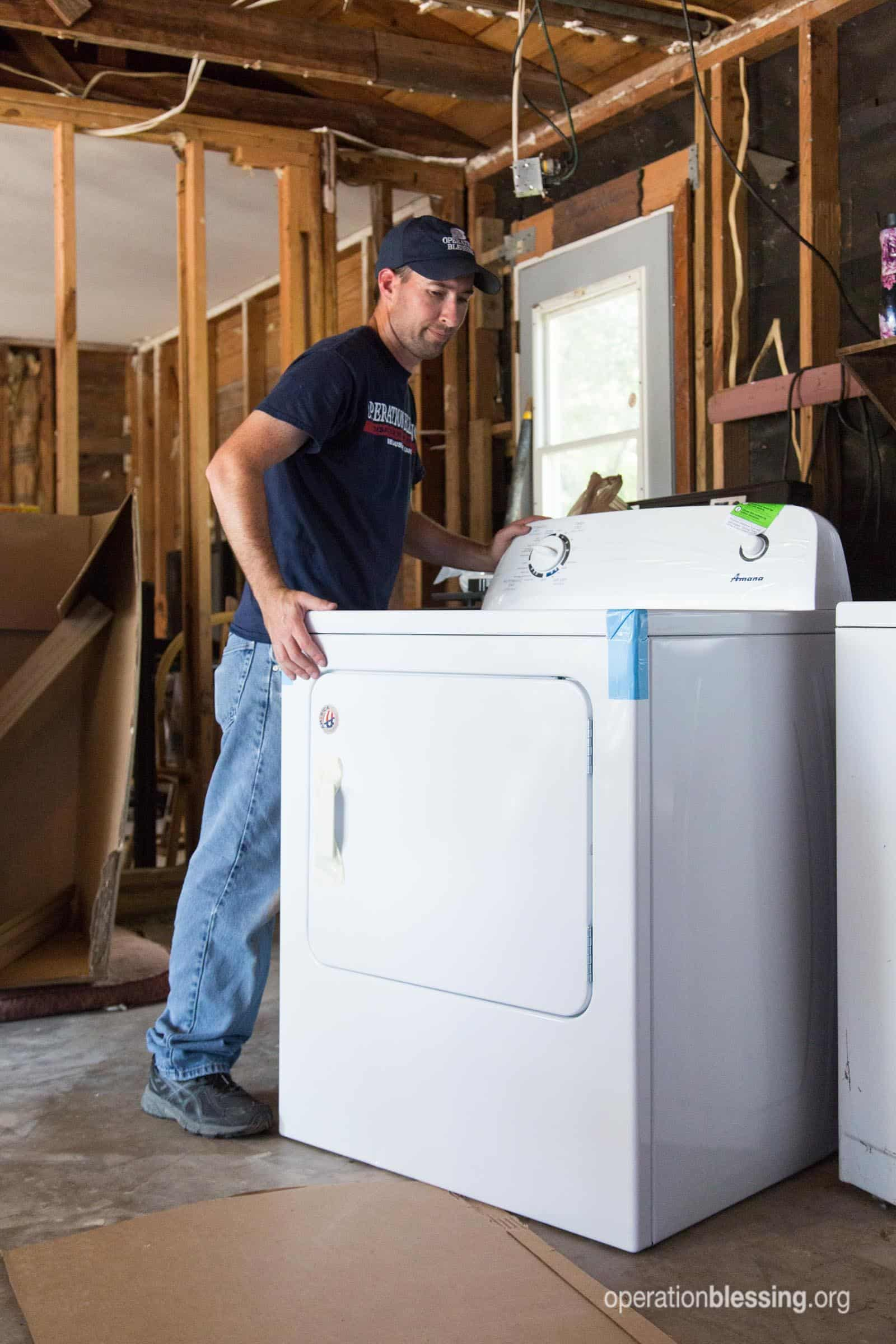An Operation Blessing team member installs the dryer for Priscilla.