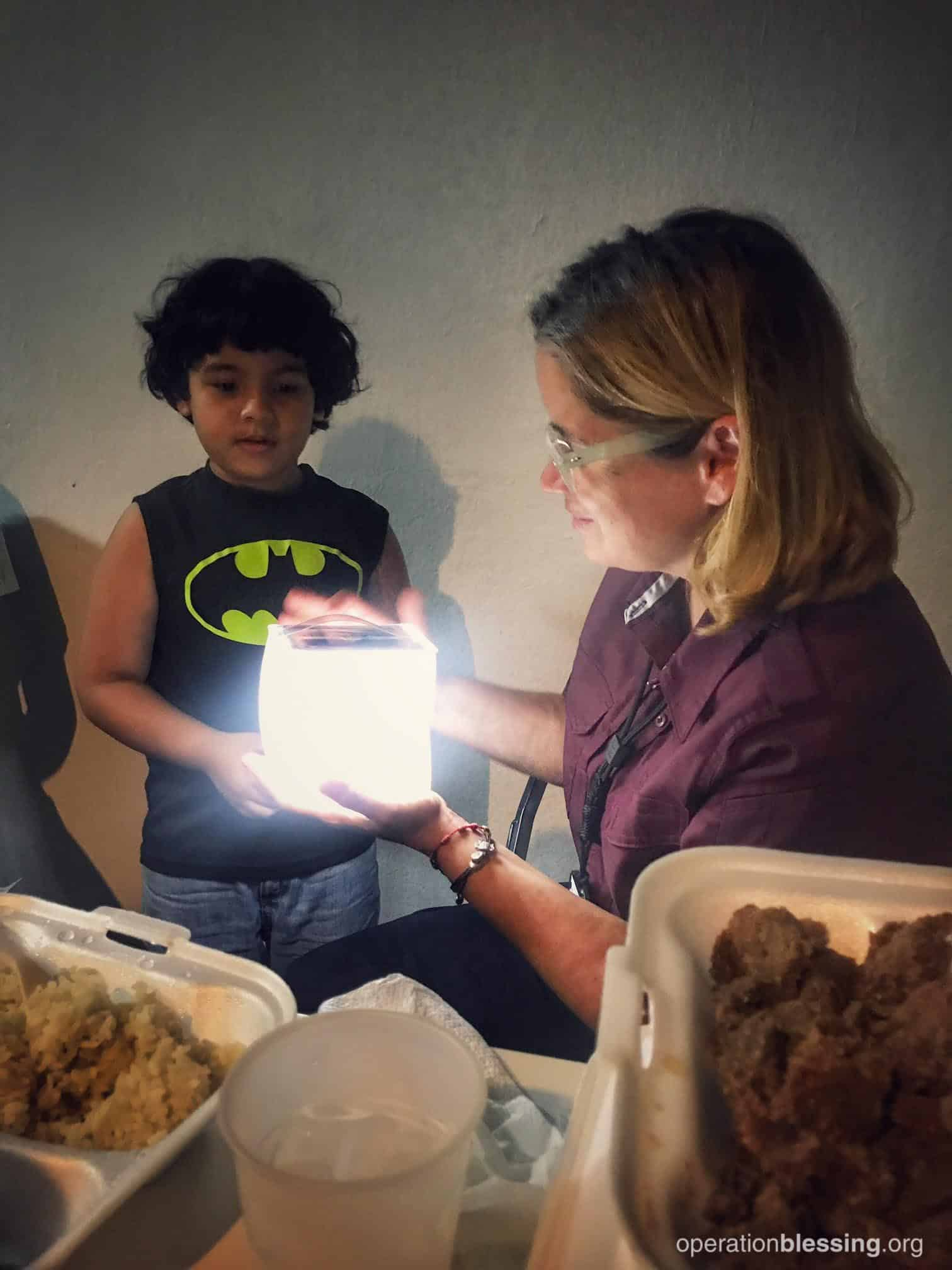 The mayor of San Juan helps distribute Operation Blessing solar lights to children in need in Puerto Rico.