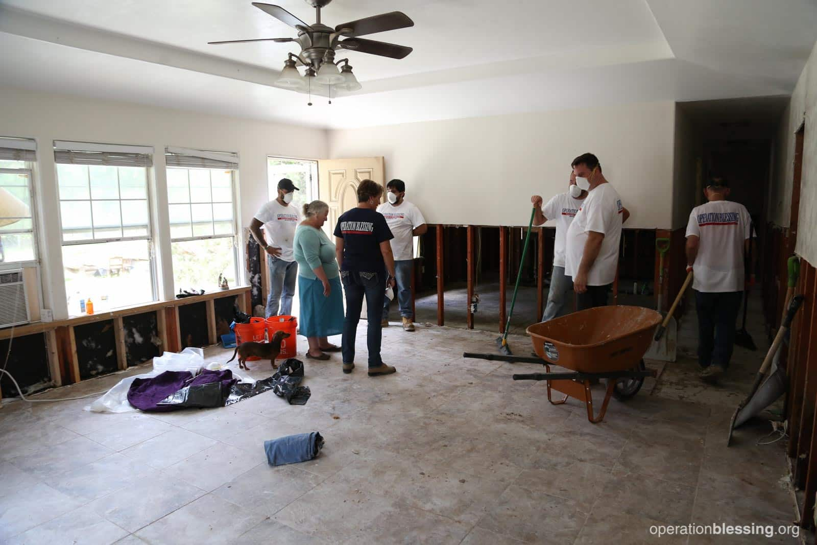 Laura and OBI workers examine the work they've done on her flood-damaged home.