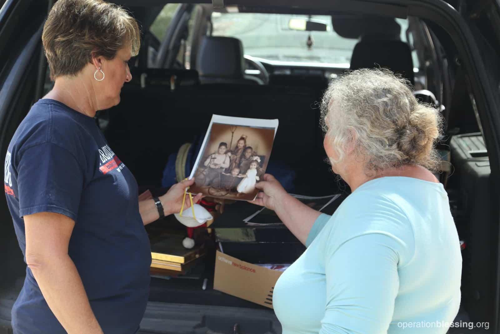 Laura shows Sheila salvaged pictures of her children and grandchildren.