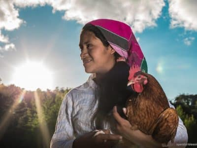 Martha holds a chicken given to her through OB Honduras's poultry project, as the sun sets behind her.
