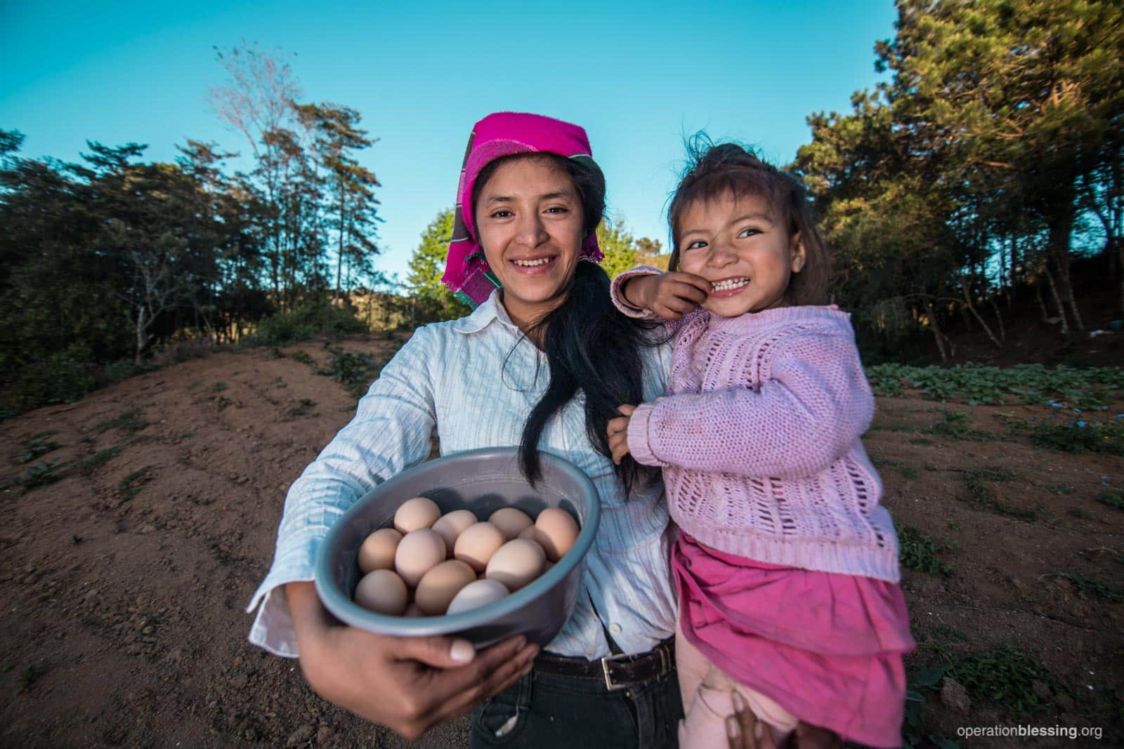 Martha holds eggs and her happy daughter thanks to an OBI poultry project.