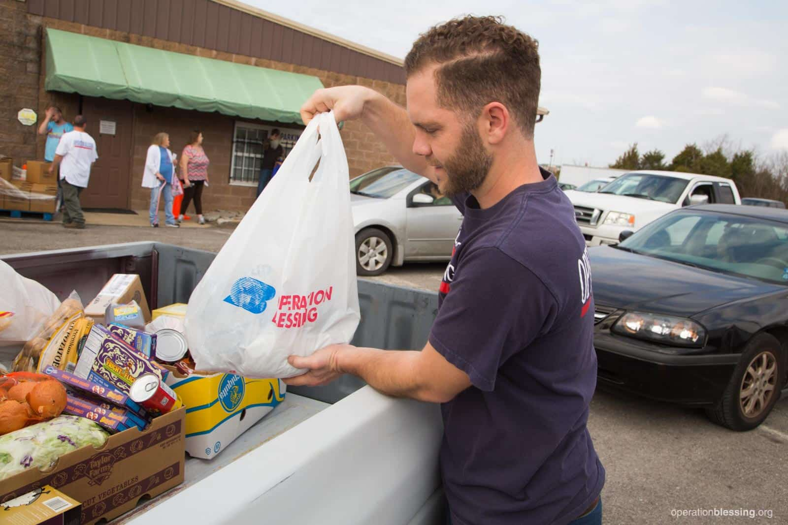 An OBI worker packs groceries into the truck of a family on the brink.