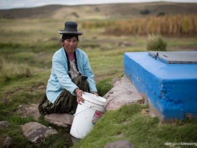 A woman gathers fresh water from the newly renovated water source. Her community highland community has been transformed.