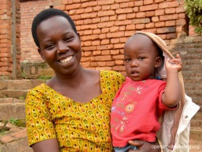 Francoise holds her formally malnourished young son, Dubudonnee, who is now thriving thanks to OBI partner, Gardens for Health.