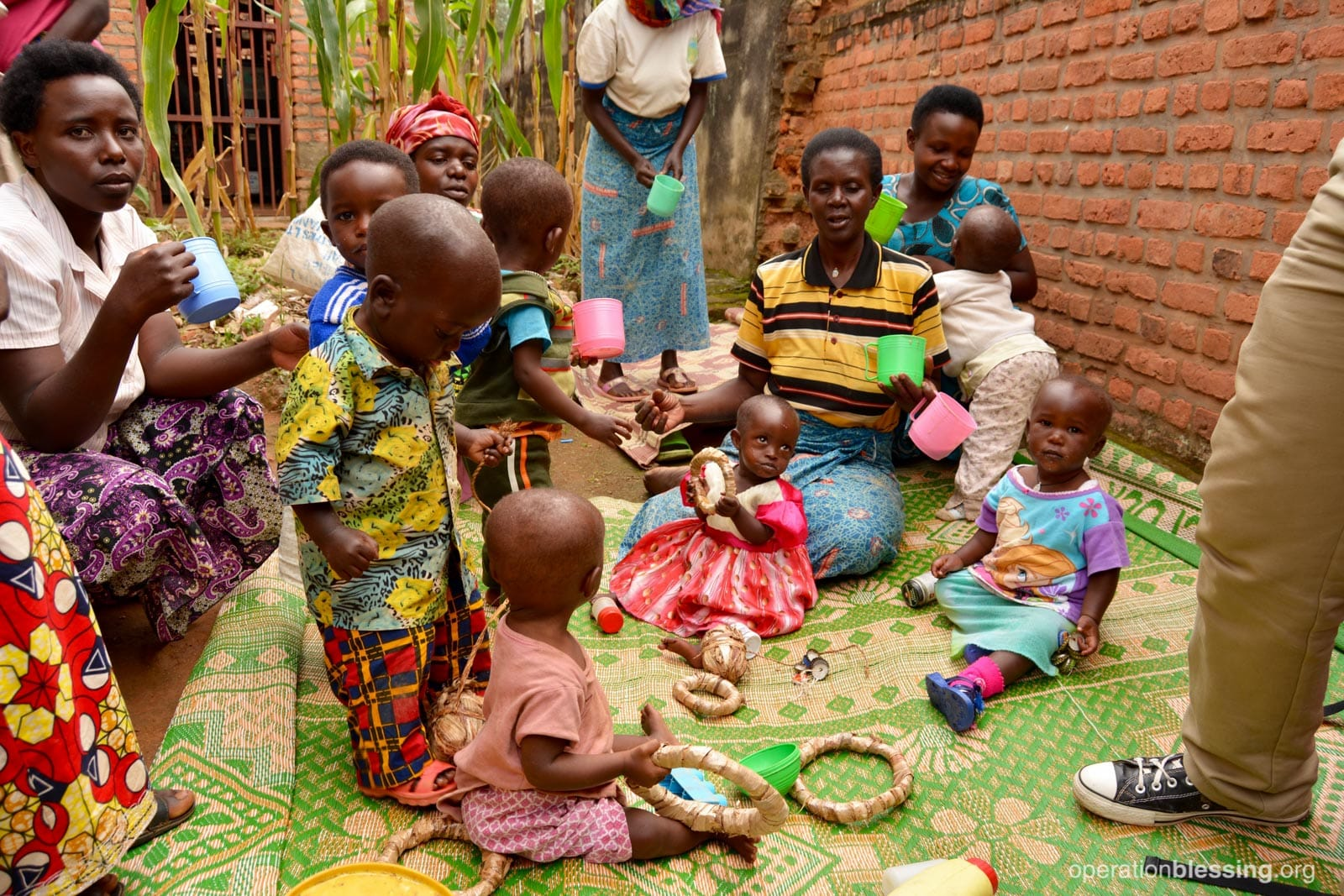 Dubudonnee and other children in the Gardens for Health program enjoy snacks and playtime with the staff while their mothers learn about good nutrition.