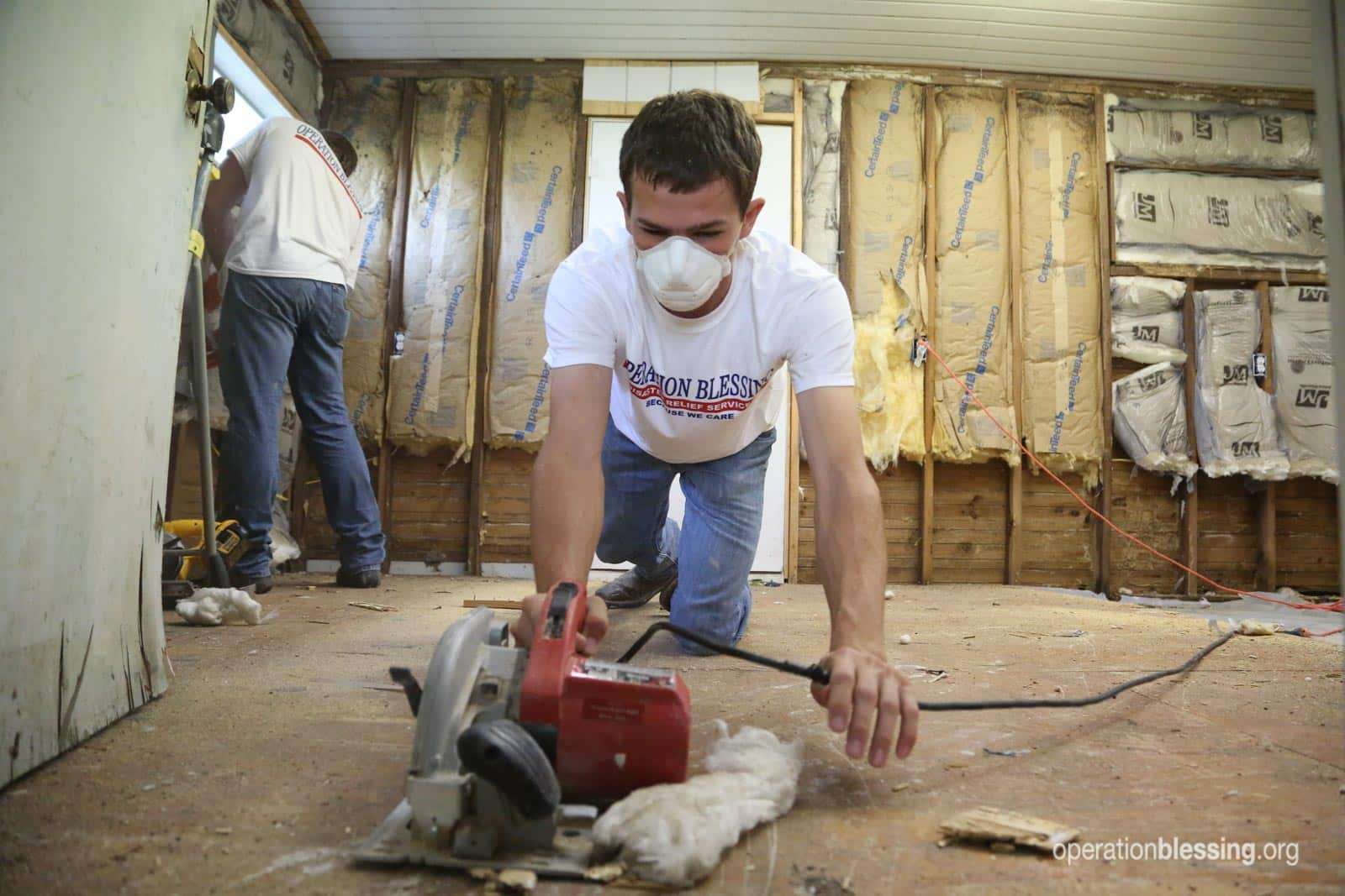 A volunteer takes out flooring in Gwendolyn's home after Hurricane Harvey