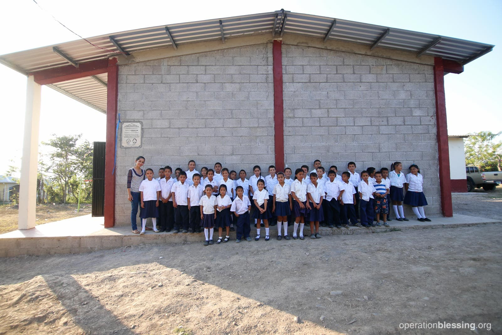 Children of Brisas de Occidente, Santa Barbara, Honduras, stand in front of a new school building from Operation Blessing.