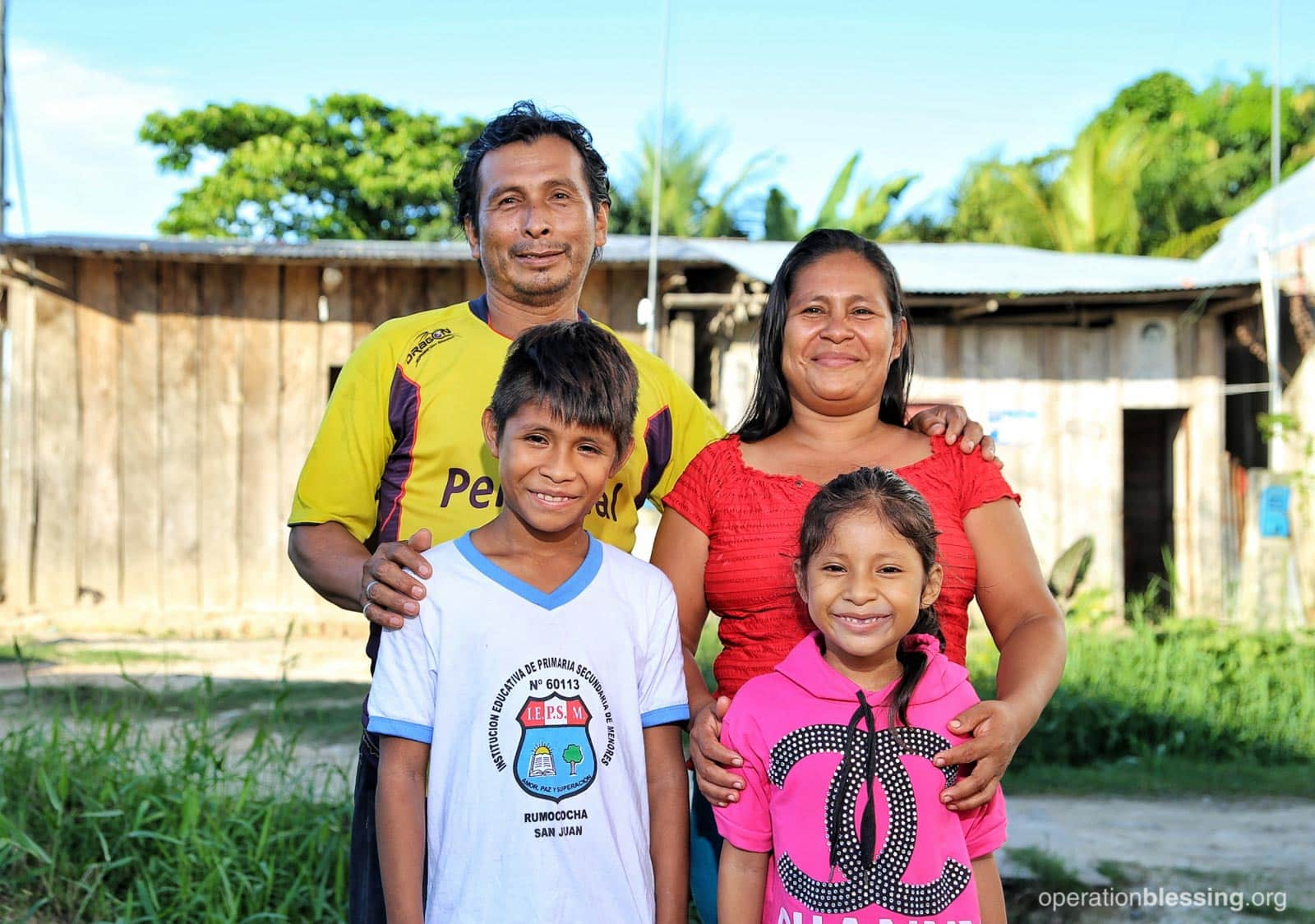 Elizabeth and Andres, pictured with two of their three children, are grateful for the education and practical gift of a chicken coop to care for and profit from.