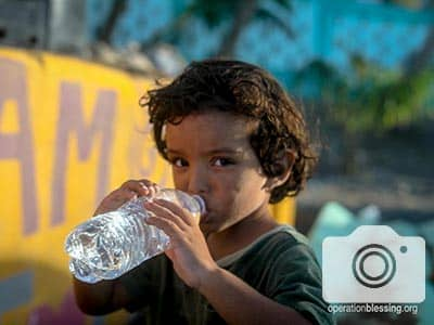 This little one drinks happily, thankful OBI is restoring safe water in La Perla.