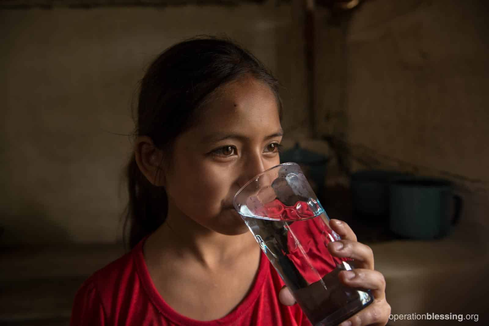 Nelly enjoys a glass of safe water thanks to Operation Blessing.