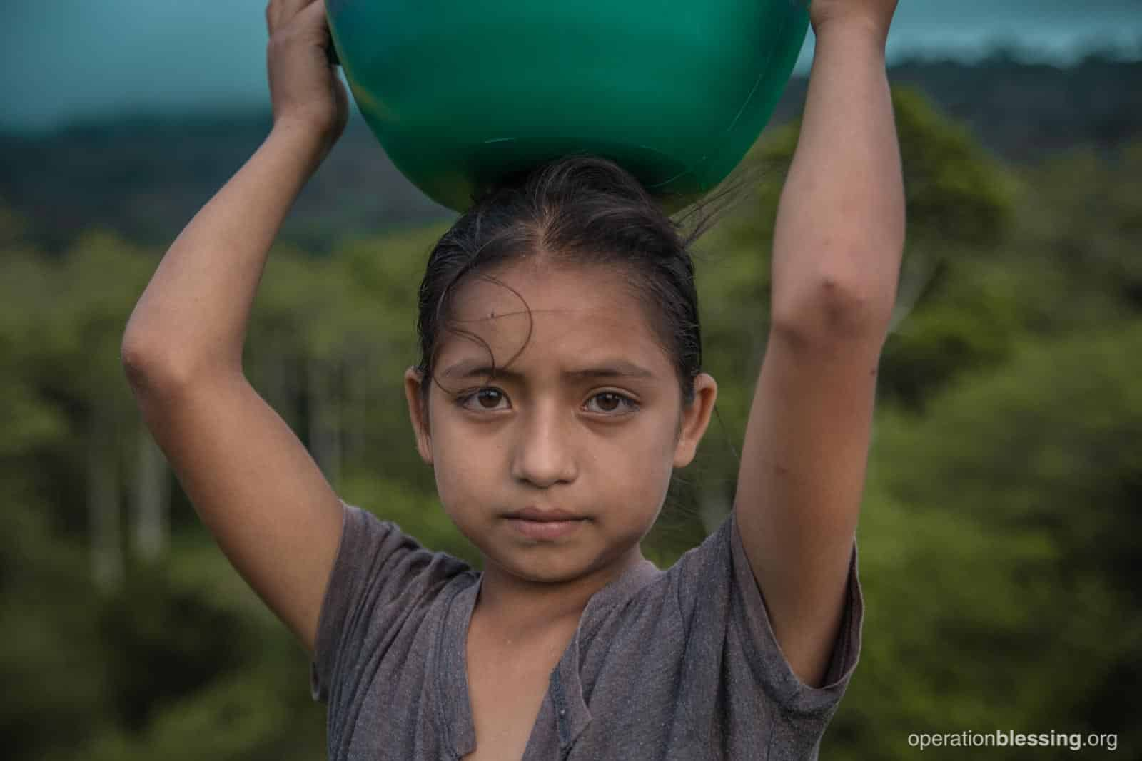 Nelly, 11, and other members of a community in rural Honduras walked long distances to retrieve small amounts of clean water.