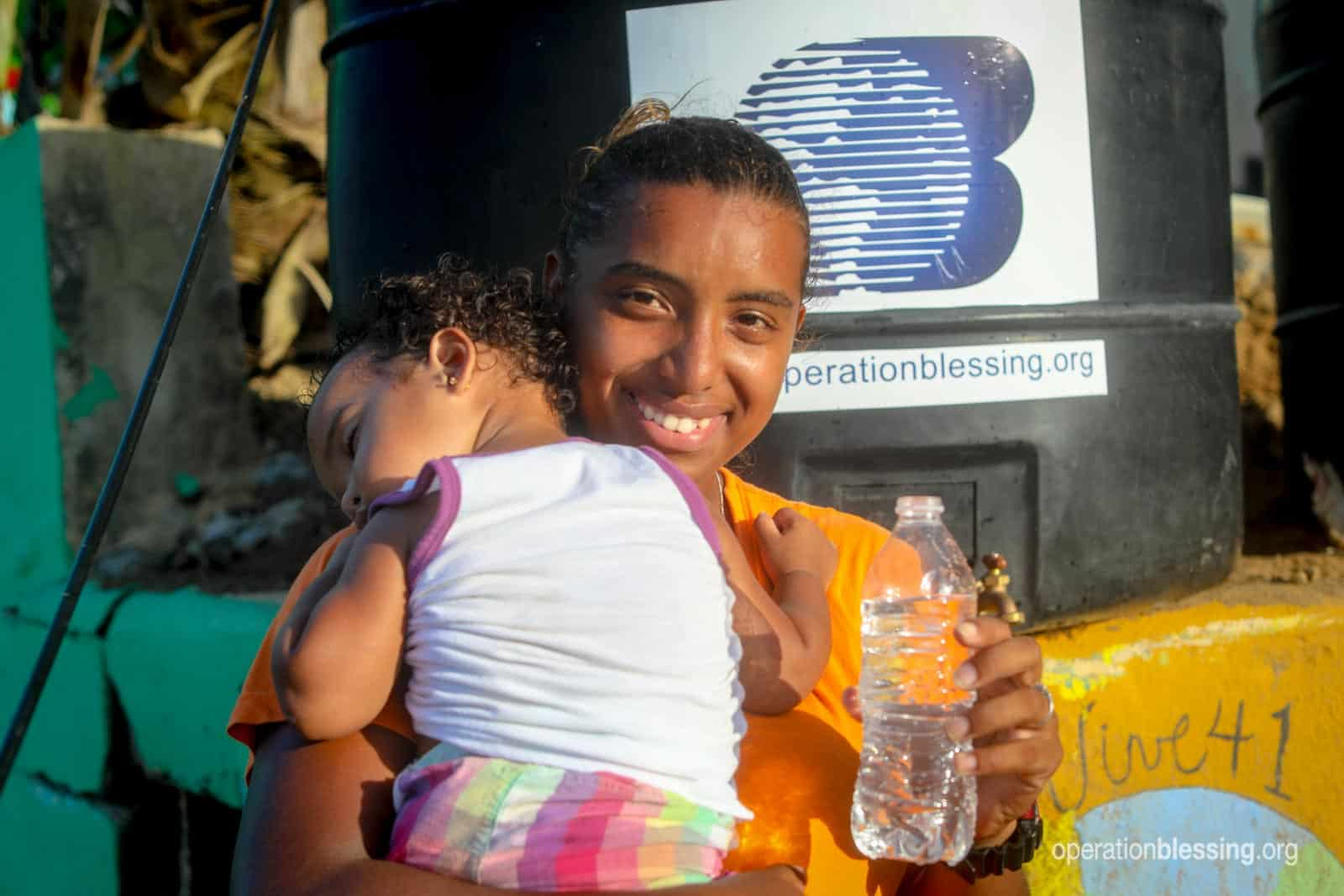 A woman stands with her child and a bottle of safe drinking water.