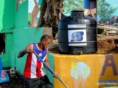 A man in front of a safe water system OBI is using to increase the safe water footprint in Puerto Rico.