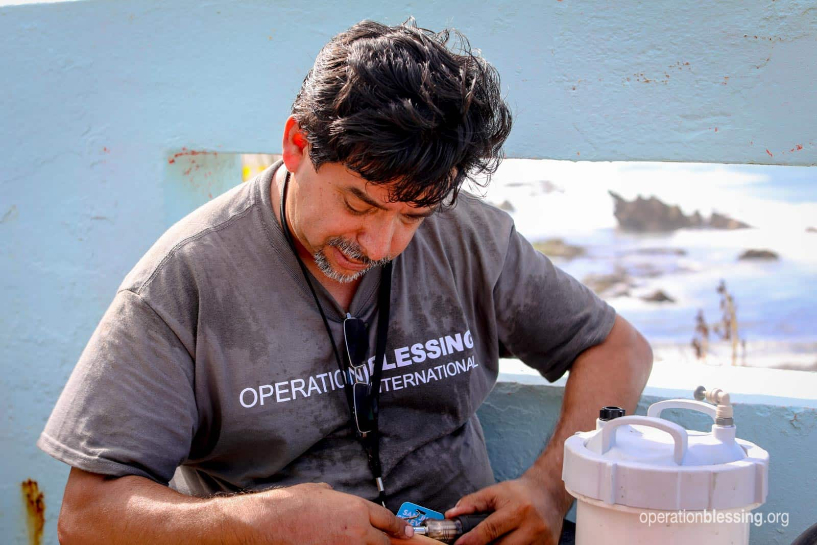 An Operation Blessing staff member gets the desalination unit up and running.