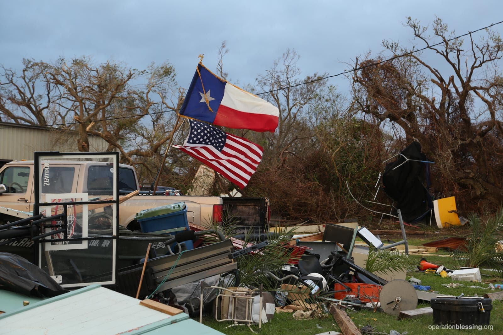 American and Texan flags fly from the back of a pickup truck amidst the devastation of Harvey, as Operation Blessing begins their disaster relief.