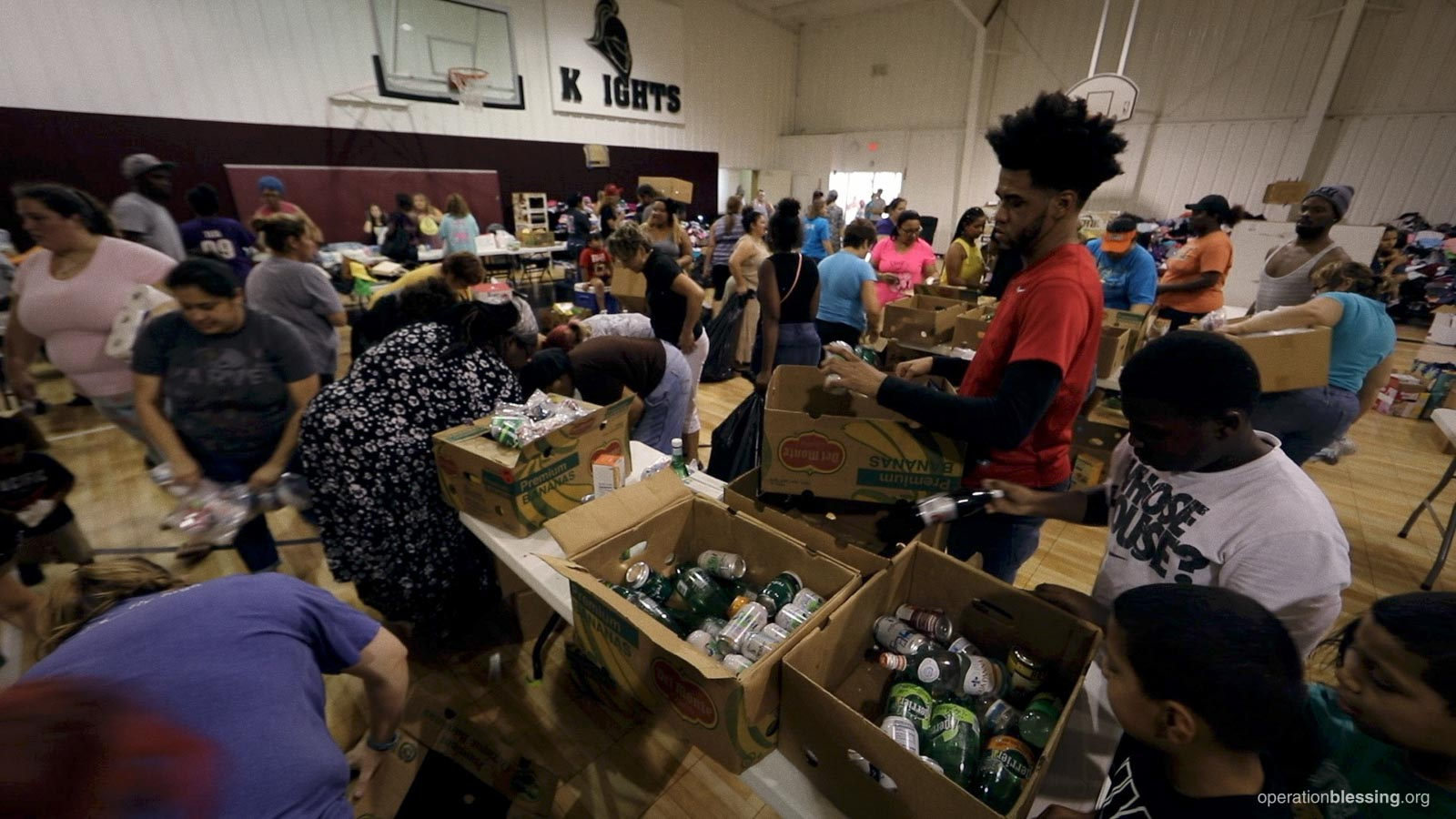 Hundreds of people seek help at an Operation Blessing food distribution.
