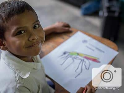 A child colors his mosquito worksheet, beating pests with an education.