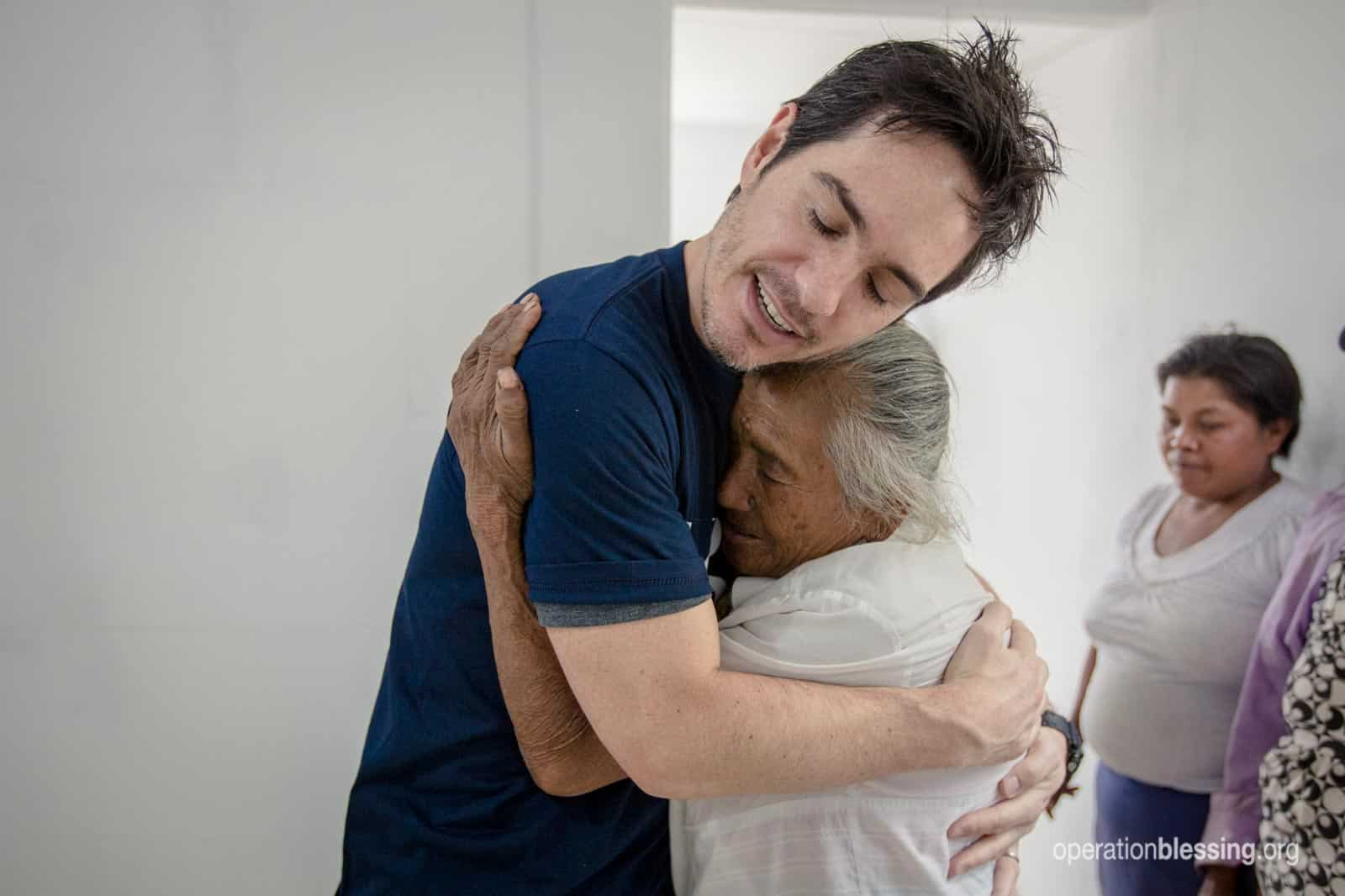 Tonita hugs one of the volunteers after a deadly earthquake took her husband and home.